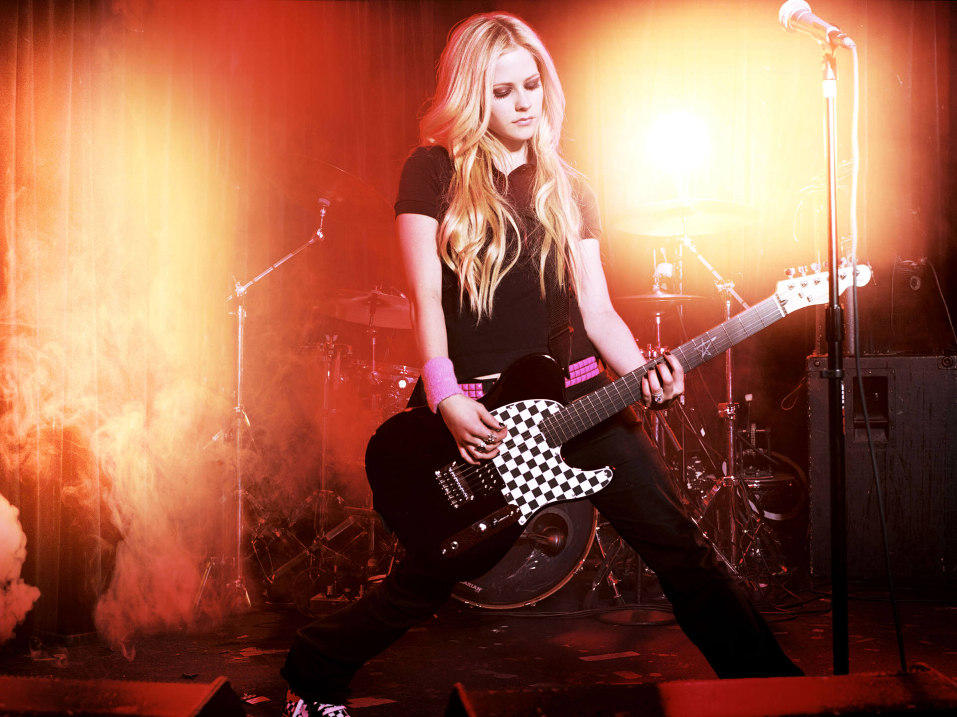 Avril Lavigne performs on stage with her guitar
